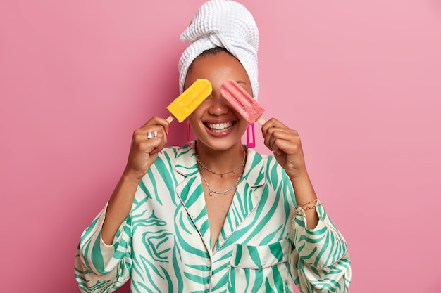 Mulher de pele escura positiva cobre os olhos com sorvetes frescos e gelados, se diverte durante o dia quente, usa robe doméstico casual e toalha de banho após tomar banho