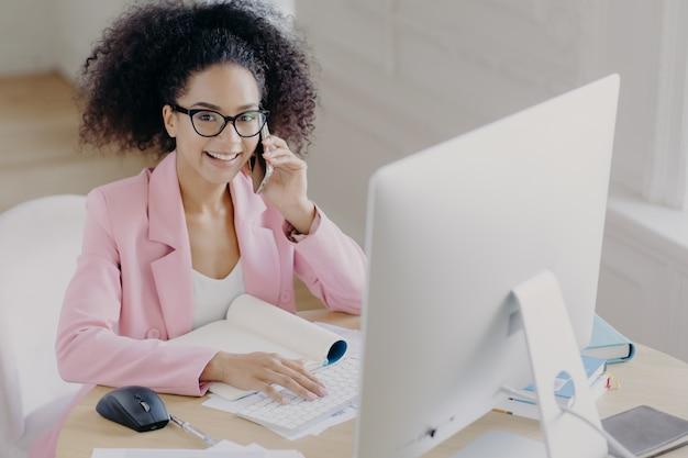 Mulher de pele escura positiva com cabelo penteado encaracolado, teclados no computador, envolvidos no processo de trabalho