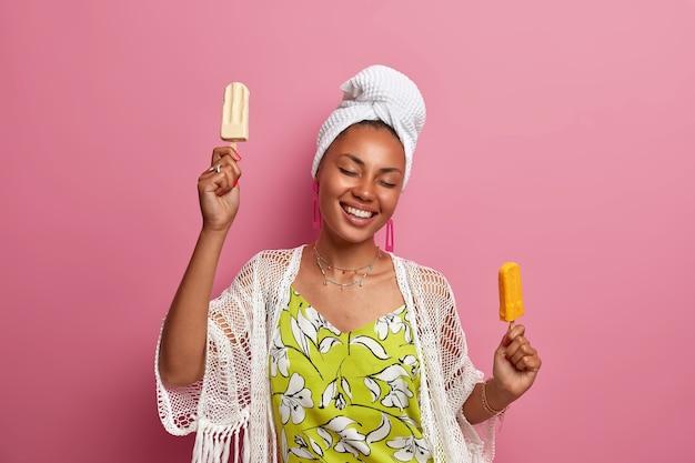 Mulher de pele escura positiva com um sorriso amplo, segurando um sorvete delicioso, mantendo os olhos fechados