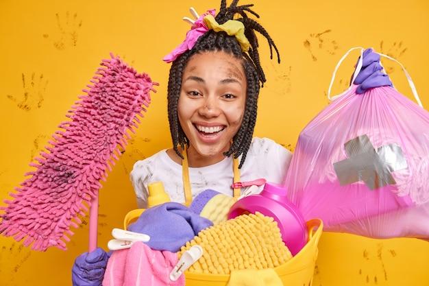 Mulher de pele escura positiva fica suja após a limpeza geral fazer o trabalho doméstico segura o saco de lixo e o esfregão sujo arruma o apartamento lava a roupa sorrisos amplamente isolados sobre a parede amarela