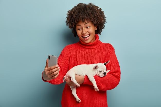 Mulher de pele escura positiva ri alegremente, posa para o celular, faz selfie segurando um cachorrinho com pedigree, usa um macacão vermelho, se diverte com o animal de estimação, cabelo encaracolado, fica contra a parede azul