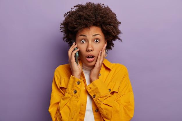 Mulher de pele escura preocupada fala em pânico pelo celular, fica sabendo das más notícias, usa camisa amarela, segura o smartphone perto da orelha