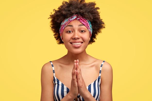 Mulher de pele escura satisfeita com expressão facial suplicante, mantém as mãos em gesto de oração, sorri positivamente, usa roupas casuais