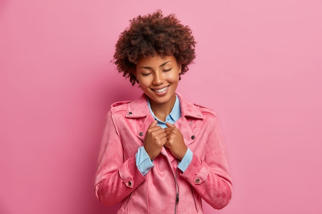 Mulher de pele escura satisfeita relembrando boas memórias mantém as mãos na jaqueta fecha os olhos e sorri agradavelmente