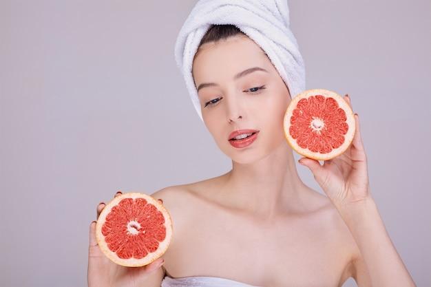 Mulher de pele limpa, seminua, com uma toalha na cabeça, tem nas mãos uma toranja fresca.