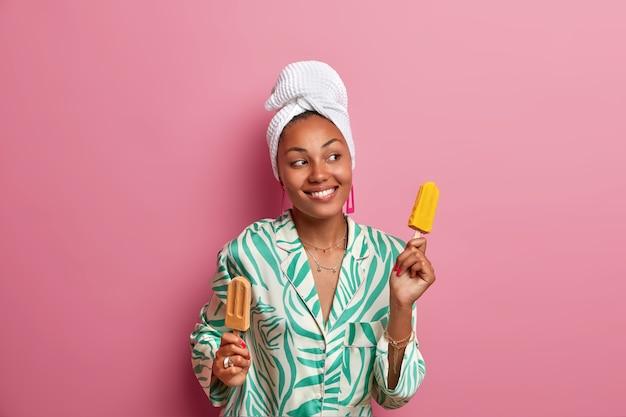 Mulher de pele morena despreocupada e simpática dança com sorvete nas mãos, tem bom humor, olha de lado e sorri amplamente, usa toalha e roupão, come sobremesa gelada gelada no verão