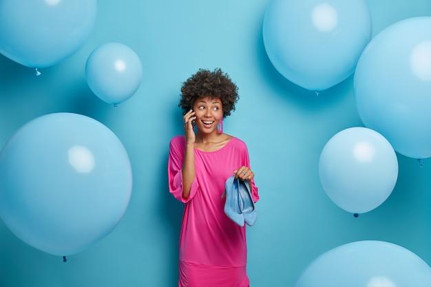 Mulher de pele morena encantada conversa ao telefone discute detalhes sobre quando e onde será a festa escolhe sapatos elegantes de salto alto encostados na parede azul prepara surpresa no feriado