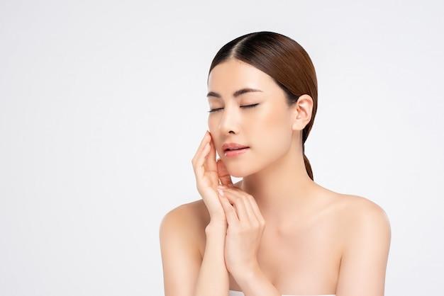 Mulher de pele saudável, tocando suavemente o rosto com a mão para o conceito de beleza