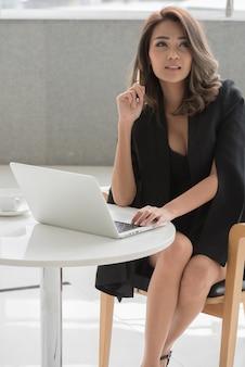 Mulher de pensamento do trabalhador de escritório que senta-se na pena de terra arrendada da mesa e que usa o computador portátil.