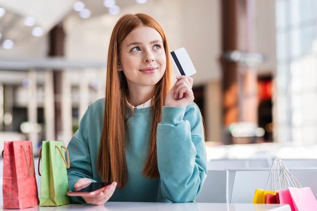 Mulher de pensamento segurando um cartão de crédito