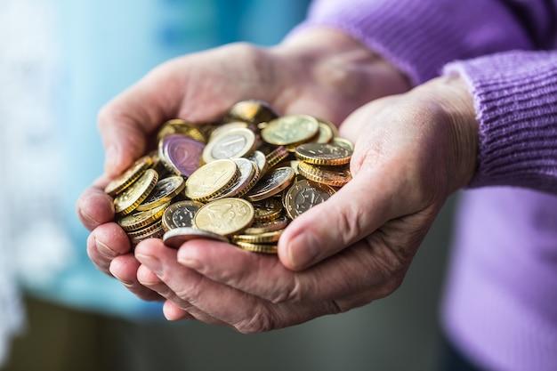 Mulher de pensionista segurando moedas de euro nas mãos. tema das pensões baixas.