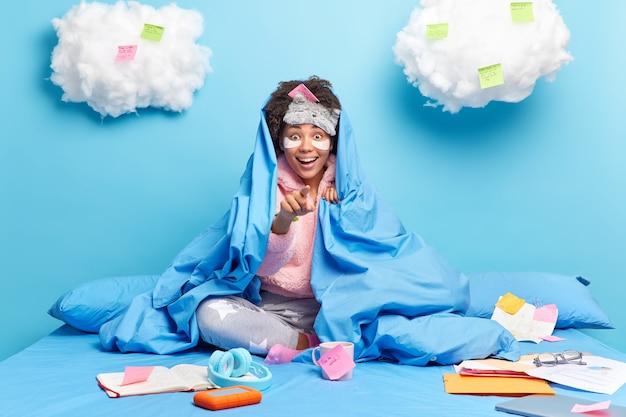 Mulher de pijama aponta com grande surpresa prepara poses de projeto criativo no quarto em cama confortável faz anotações em adesivos trabalhos de casa