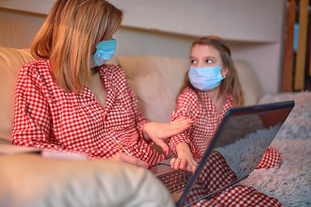Mulher de pijama com caderno e papéis, trabalhando em casa, usando máscara protetora, enquanto a filha e a filha jogam videogame