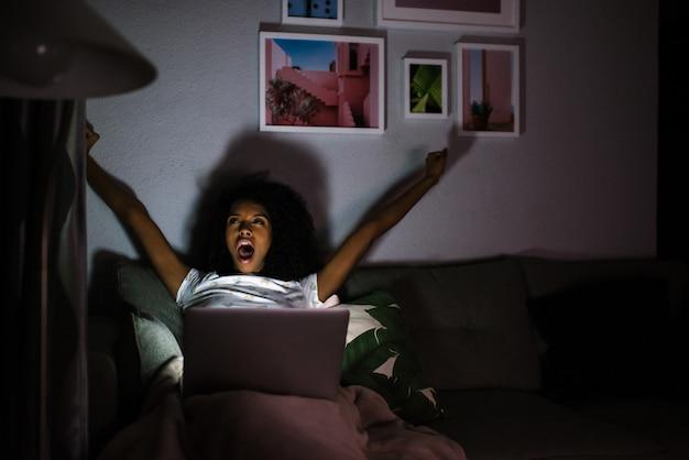 Mulher de pijama com um alongamento de computador