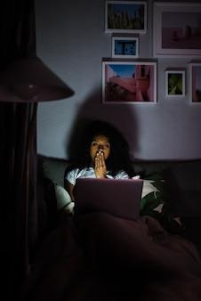 Mulher de pijama com um computador bocejando