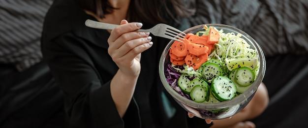 Mulher de pijama na cama com salada de vegetais fresca vegetariana.