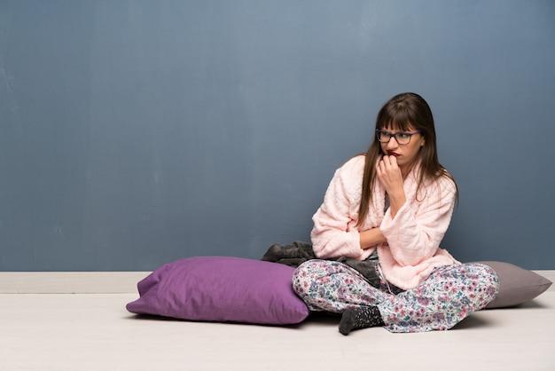 Mulher de pijama no chão com dúvidas