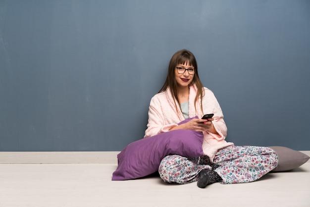 Mulher de pijama no chão enviando uma mensagem com o celular