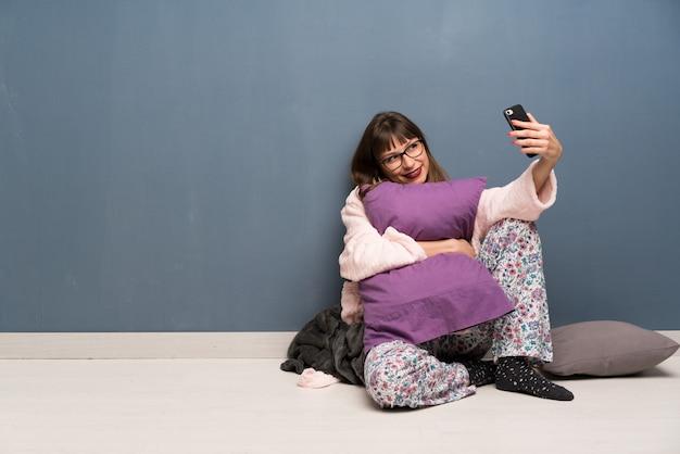 Mulher de pijama no chão fazendo um selfie
