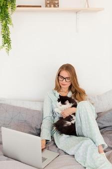 Mulher de pijama, trabalhando em casa, no laptop, segurando o gato