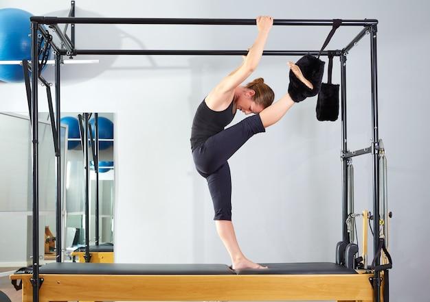 Mulher de pilates em pernas de cadillac dividir o exercício de estiramento