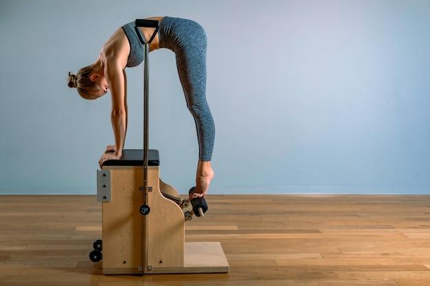 Mulher de pilates em um reformador de cadillac, fazendo exercícios de alongamento no ginásio