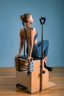 Mulher de pilates em um reformador fazendo exercícios de alongamento no ginásio. conceito de fitness, equipamento especial de fitness, estilo de vida saudável, plástico. copie o espaço, banner esporte para publicidade