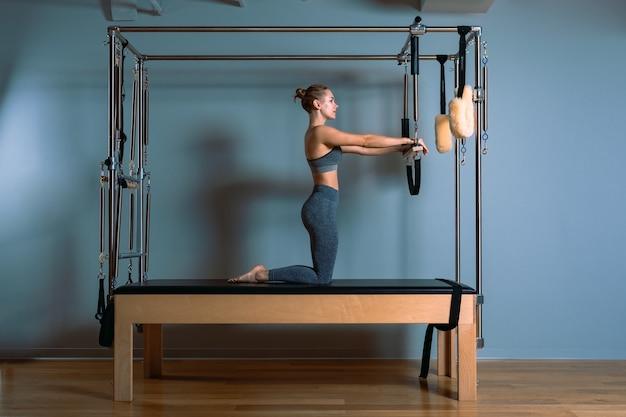 Mulher de pilates fazendo exercícios de provocação do reformador na academia dentro de casa