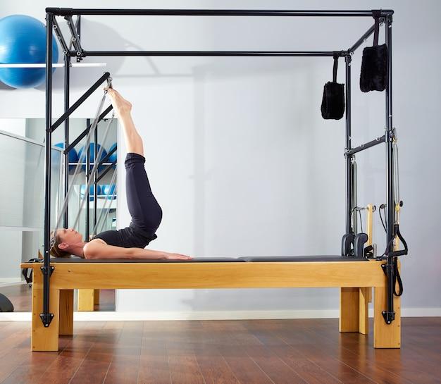 Mulher de pilates no exercício de torre de reformador no ginásio
