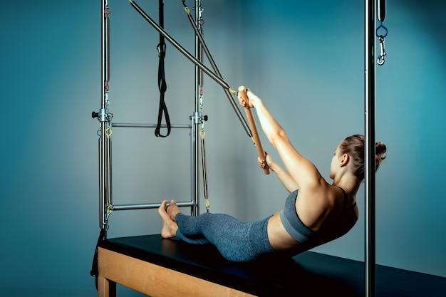 Mulher de pilates reformador cama closeup e instrutor fazendo exercício no simulador reformador