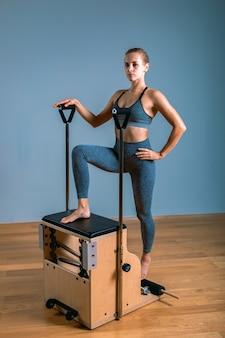 Mulher de pilates reformadora fazendo exercícios de alongamento na academia