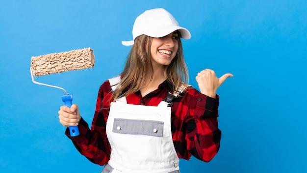 Mulher de pintor em azul isolado, apontando para o lado para apresentar um produto