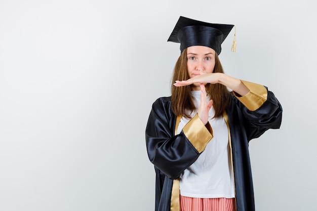 Mulher de pós-graduação em roupas casuais, uniforme, mostrando o gesto de intervalo de tempo e olhando confiante, vista frontal.
