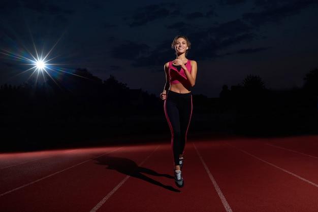 Mulher de positividade executando o treinamento no estádio durante a noite.