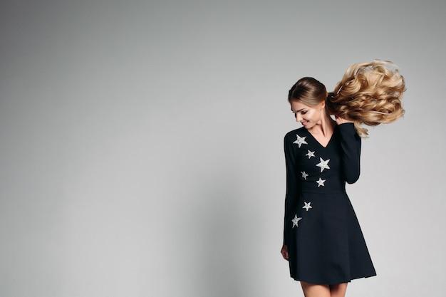 Mulher de positividade no elegante vestido preto com estrelas dançando.