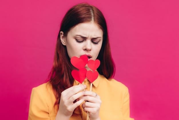 Mulher de presentes de dia dos namorados com coração na vara na parede rosa copie o espaço.