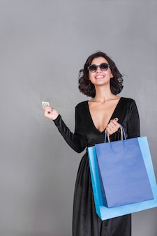 Mulher de preto com sacolas brilhantes e cartão de crédito