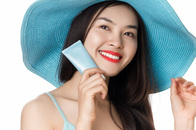 Mulher de protetor solar com chapéu de palha azul segurando um tubo de creme bronzeador isolado no branco.