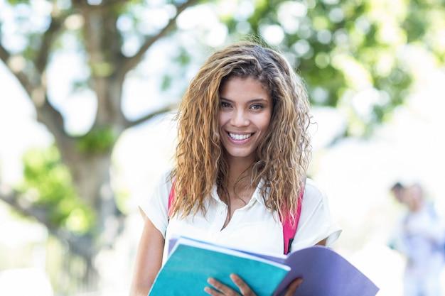 Mulher de quadril segurando o caderno e sorrindo para a câmera na cidade