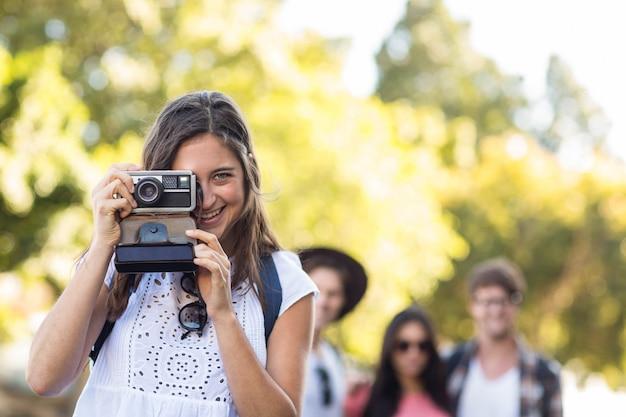 Mulher de quadril tirando foto da câmera ao ar livre