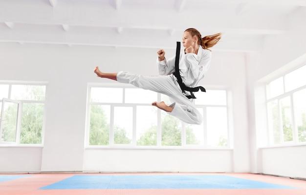 Mulher de quimono branco com faixa preta pulando e realizando chute.