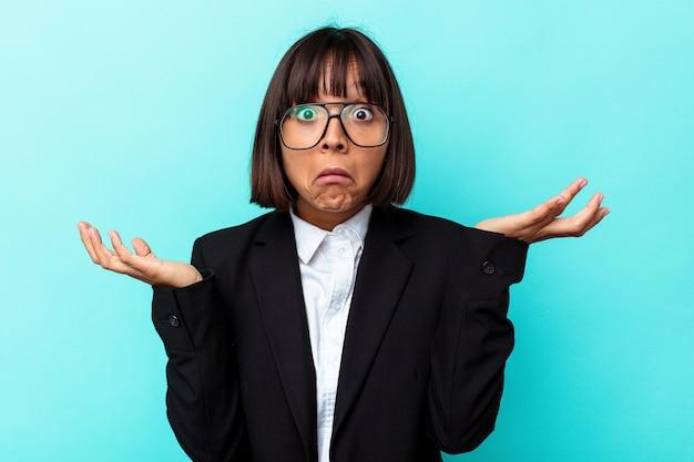 Mulher de raça mista de negócios jovem isolada em fundo azul encolhe os ombros e abre os olhos confusos.