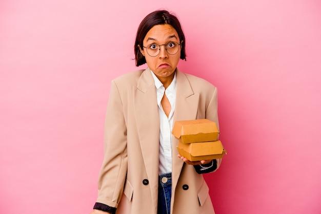 Mulher de raça mista de negócios jovem isolada em fundo rosa encolhe os ombros e abre os olhos confusos.