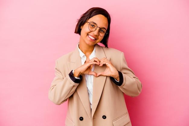 Mulher de raça mista de negócios jovem isolada em fundo rosa, sorrindo e mostrando uma forma de coração com as mãos.