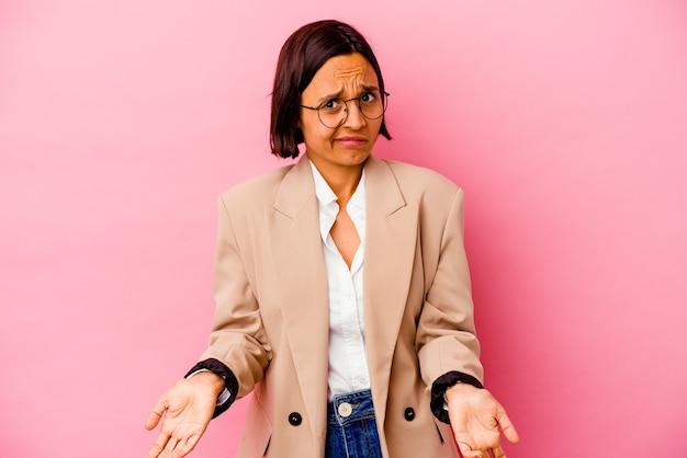 Mulher de raça mista de negócios jovem isolada na parede rosa encolhe os ombros e abre os olhos confusos.