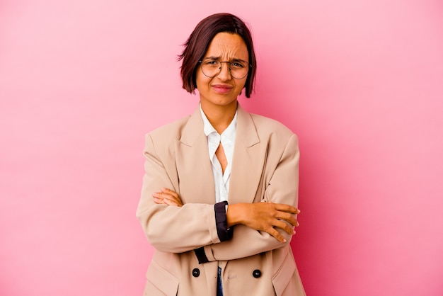 Mulher de raça mista de negócios jovem isolada na parede rosa suspeita, incerta, examinando você.