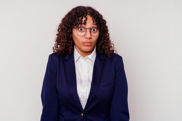 Mulher de raça mista de negócios jovem isolada no branco encolhe os ombros e abre os olhos confusos.