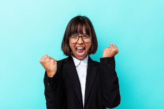 Mulher de raça mista de negócios jovem isolada sobre fundo azul, levantando o punho após uma vitória, o conceito de vencedor.
