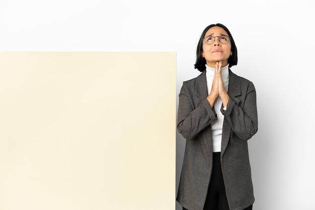 Mulher de raça mista de negócios jovens com um grande banner sobre fundo isolado mantém as palmas das mãos juntas. pessoa pede algo