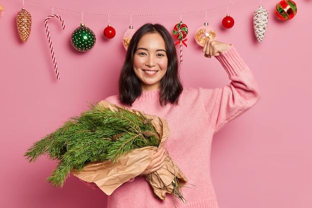 Mulher de raça mista feliz segura um buquê de galhos de árvore de abeto, levanta o braço e mostra o quão forte ela está vestida